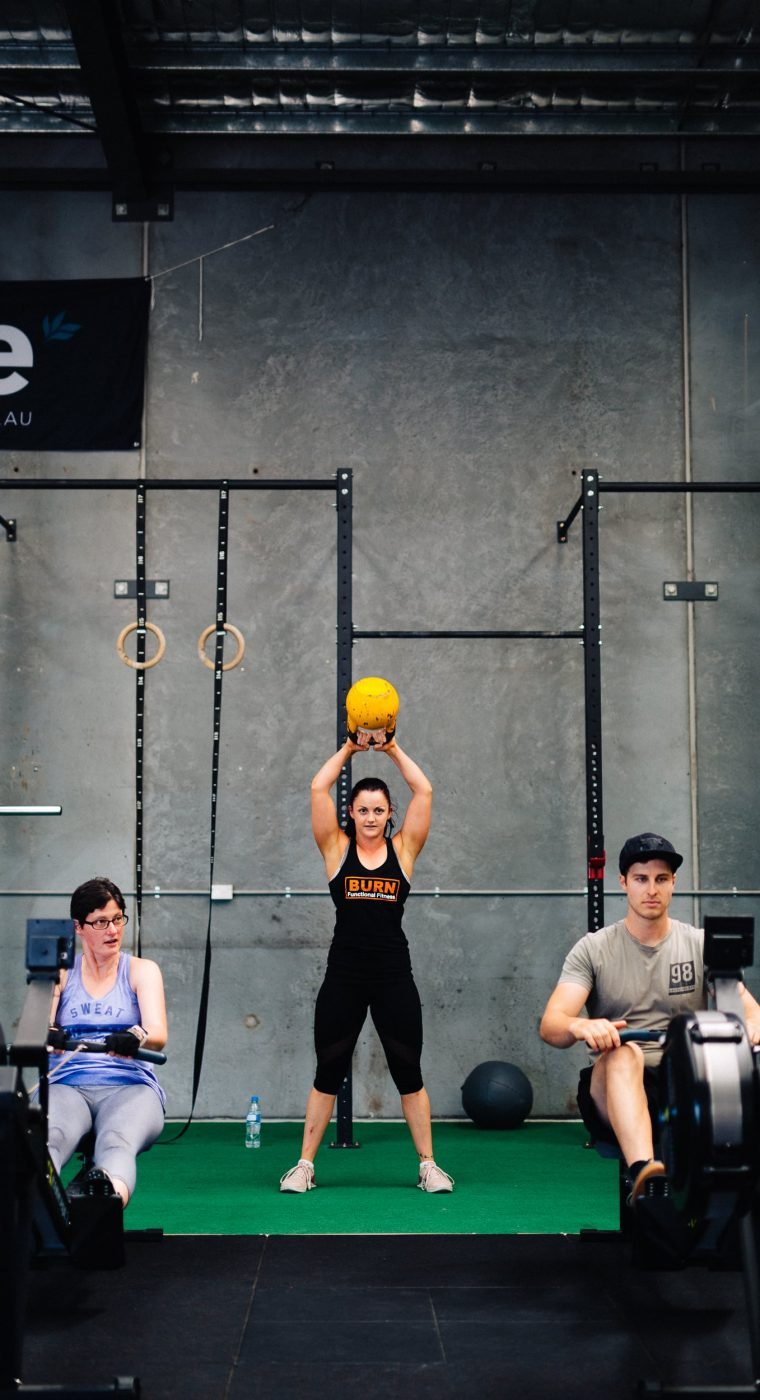 A woman holding a dumbbell above her head as people exercise around her