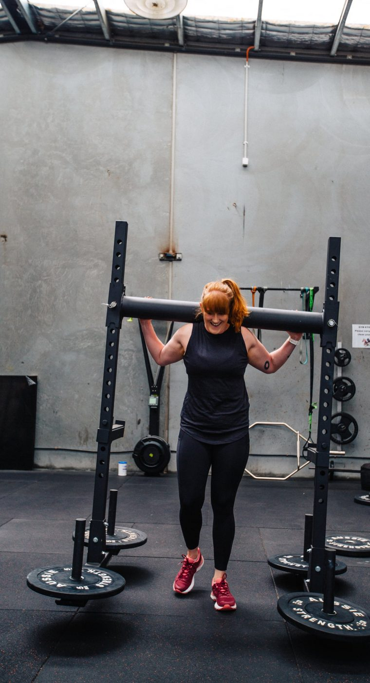 A woman smiling as she holds weights above her shoulders
