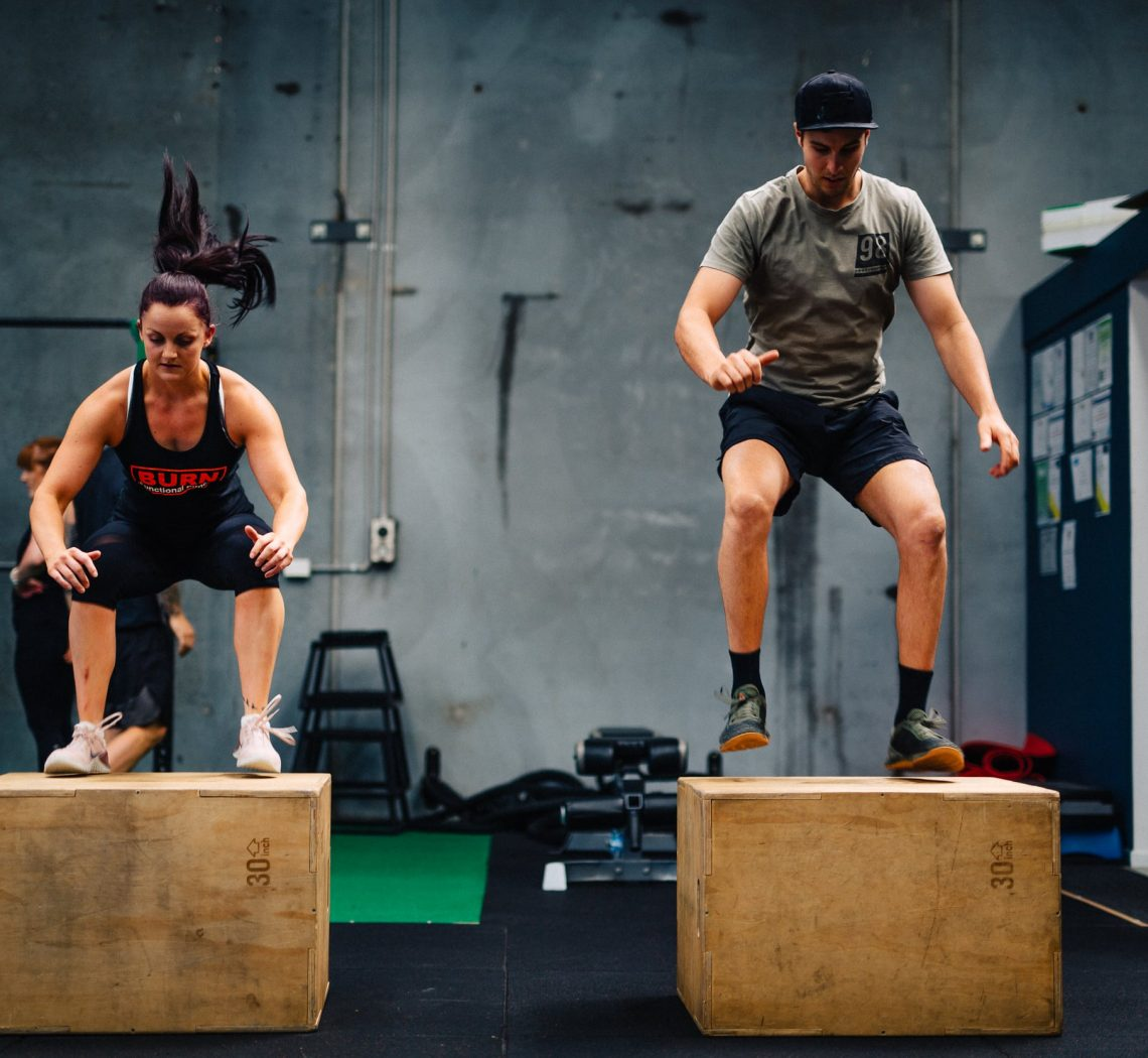 A man and female midair performing jumping jacks onto boxes