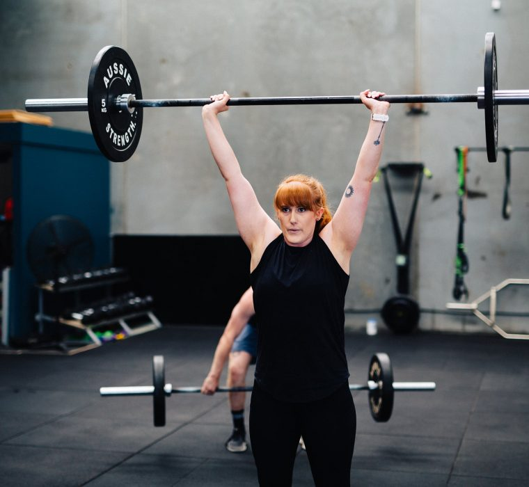 Female athlete holding weights above her head