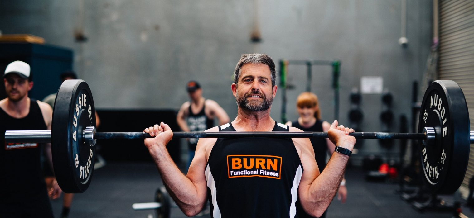 Male gym member grunting with weights between his hands