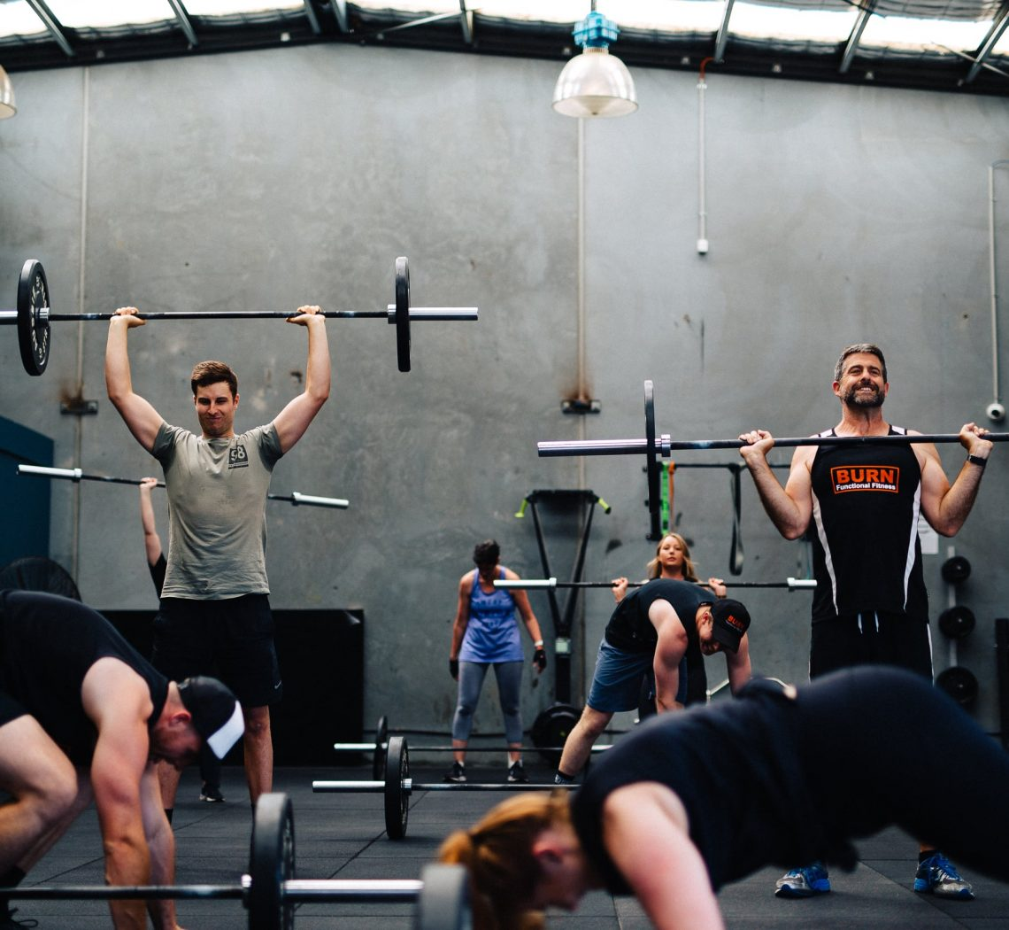 Group of people doing different weight training exercises together