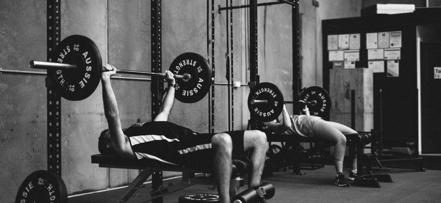 Two people, a man and woman weight-training together