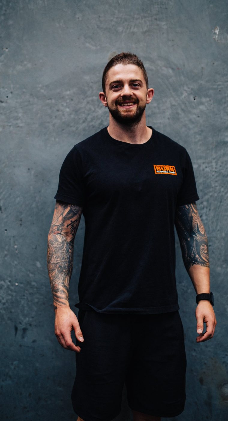 Smiling personal trainer looking at the camera against a concrete background