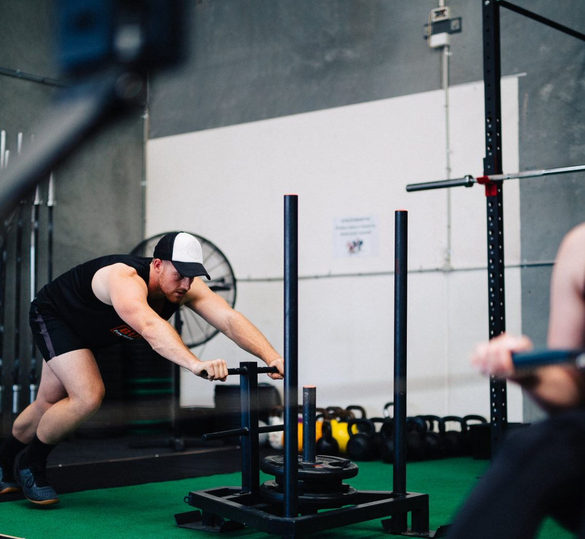 A man pushing weights across the floor of a gym