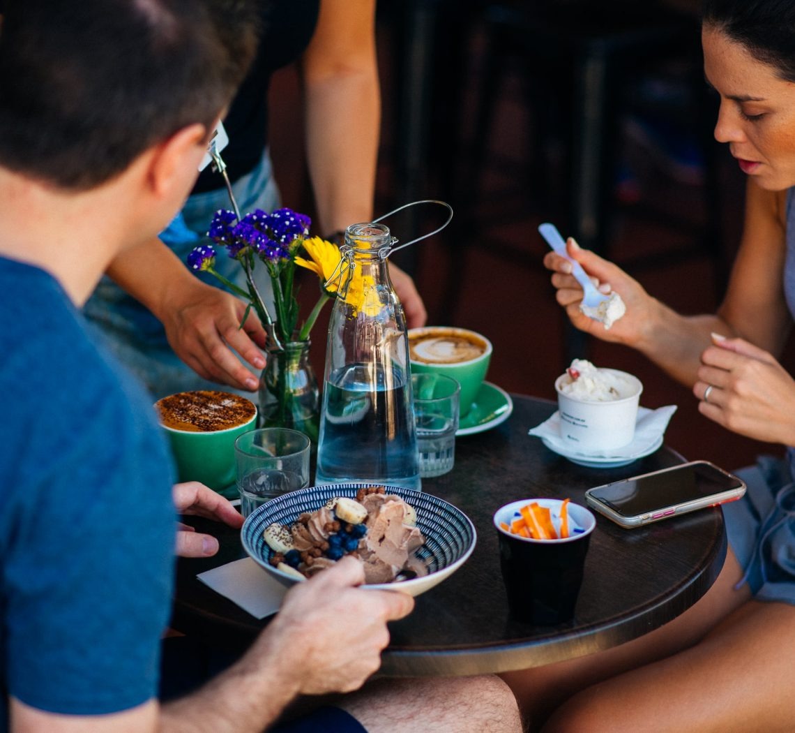 Man and woman being served coffees as the woman eats her ice-cream