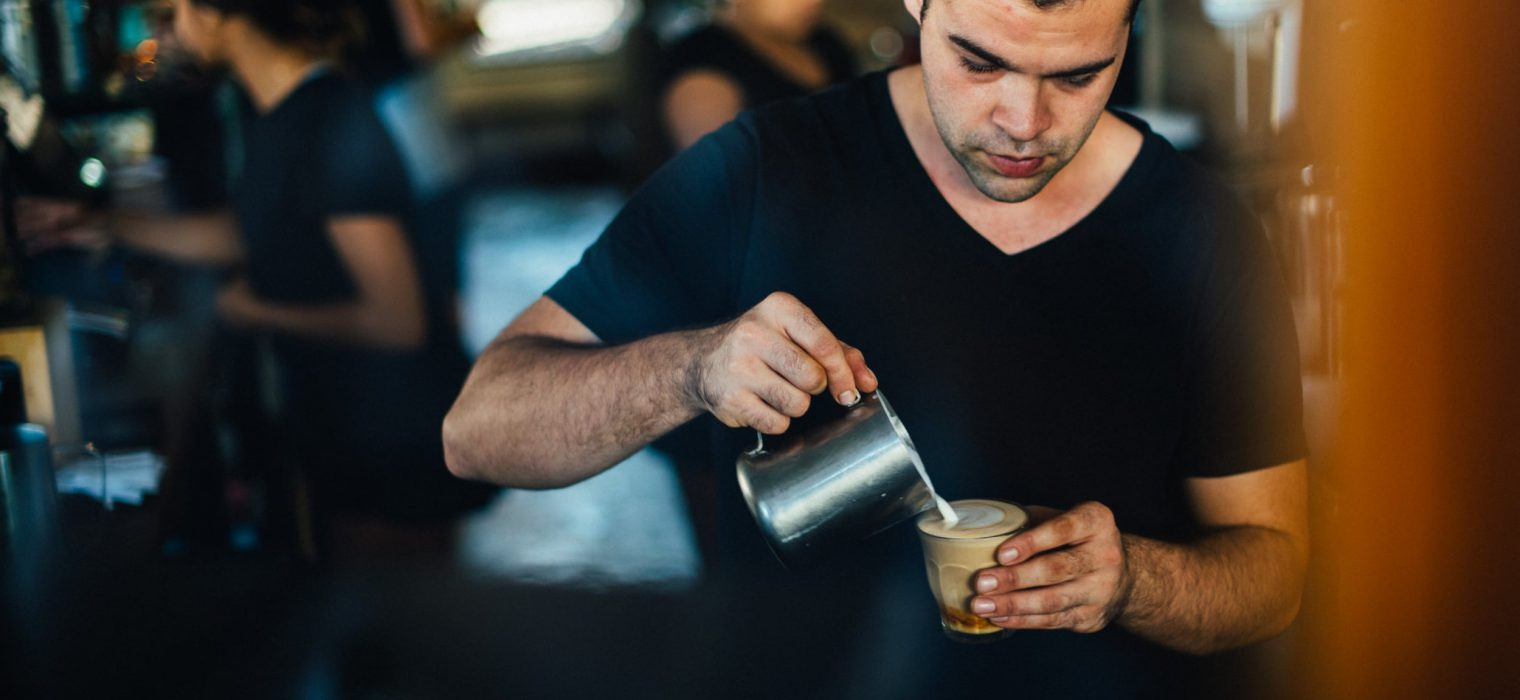 Barista pouring milk into a glass filled with expresso coffee