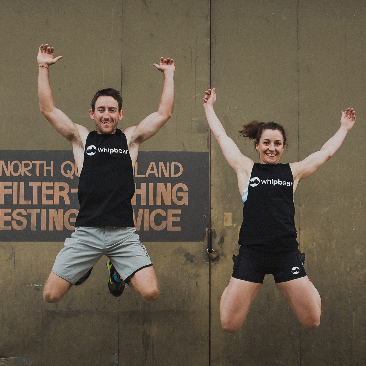 Happy man and woman jumping for joy wearing Whipbear apparel
